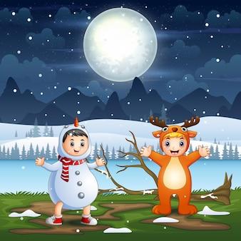 Crianças felizes em fantasias de animais na paisagem noturna de neve