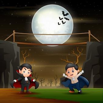 Crianças felizes em traje de vampiro na paisagem de halloween