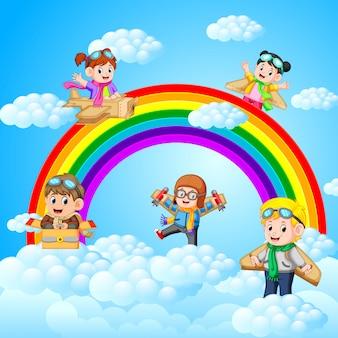 Crianças felizes jogando avião de papelão com fundo de paisagem do céu