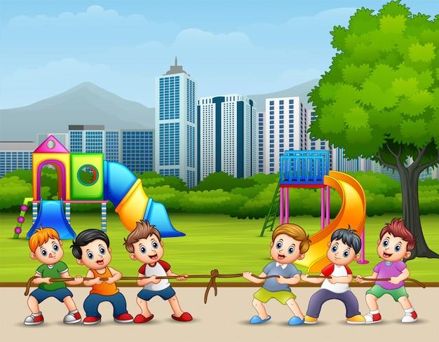 Crianças felizes jogando cabo de guerra no parque da cidade