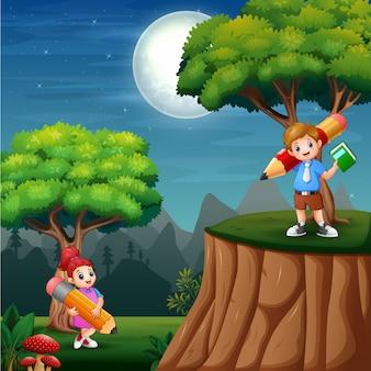 Crianças felizes, segurando um lápis grande na natureza à noite