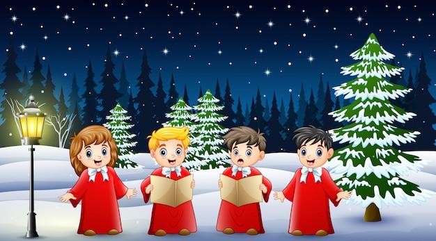 Crianças felizes vestindo traje vermelho cantando no jardim a nevar