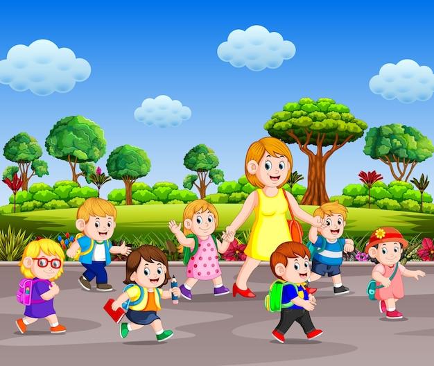 Crianças indo para a escola com seu professor andando na rua no dia ensolarado