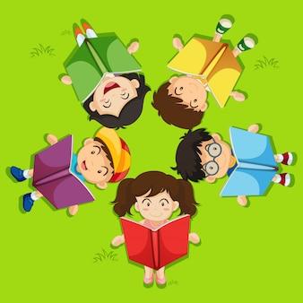 Crianças lendo livro na grama verde