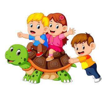 Crianças montando tartaruga gigante