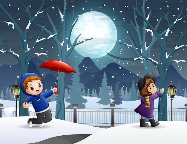 Crianças na paisagem noturna de inverno