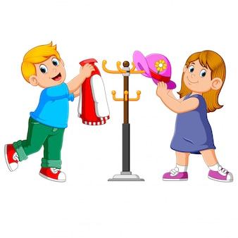 Crianças pendurando jaqueta e chapéu em carrinhos de cabide