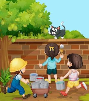 Crianças pintando parede de tijolos no jardim