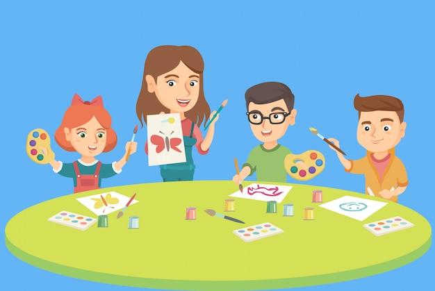 Crianças que desenham com o professor na classe pré-escolar.