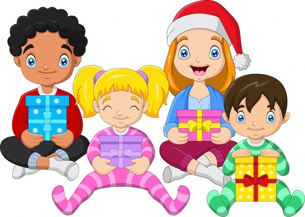 Crianças sentadas enquanto abraçam presentes