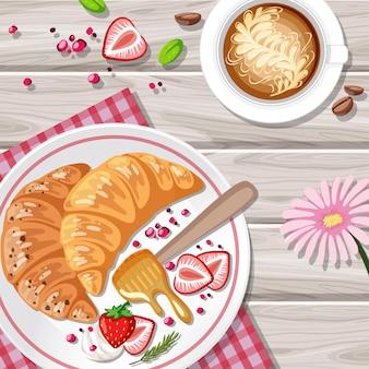 Croissant de café da manhã com frutas e uma xícara de café na mesa