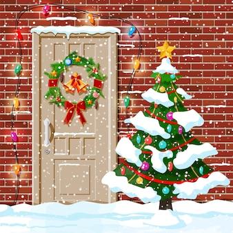 Decoração de porta de natal com neve e árvore