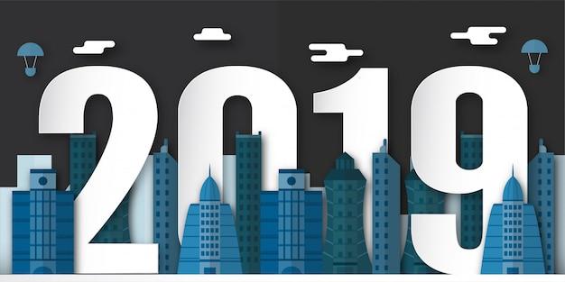 Decoração do ano novo feliz 2019 na noite com a cidade urbana no ofício cortado e digital do papel.