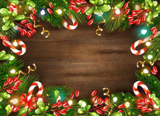 Decorações de natal brilhante com folhas de doces e luzes de fada no fundo de madeira marrom realista