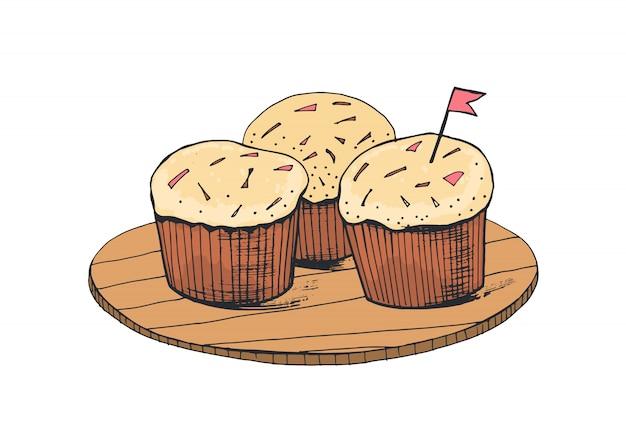 Deliciosos bolos doces ou bolinhos deliciosos, deitado na placa de madeira, isolada no fundo branco. apetitosa sobremesa assada decorada com creme, granulado e pequena bandeira.