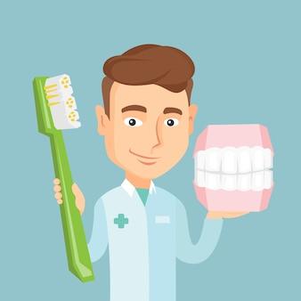 Dentista com modelo de mandíbula dental e escova de dentes.