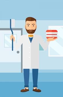 Dentista com modelo de maxila dental e escova de dentes.