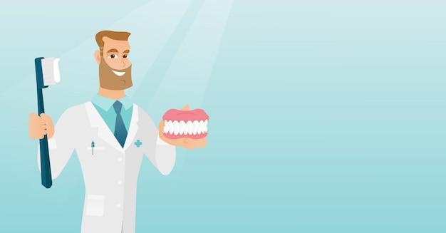 Dentista com um modelo de mandíbula dental e uma escova de dentes.