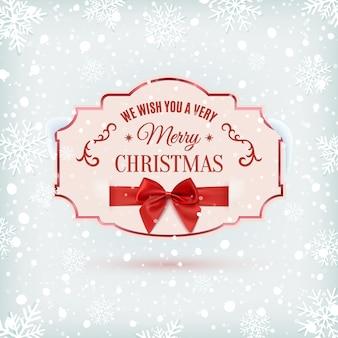 Desejamos a você um banner ornamentado de muito feliz natal com fita vermelha e um arco, em fundo de inverno com neve e flocos de neve.