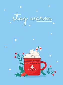 Desejando ficar aquecido com o copo de azevinho e caneca chrismtas com doces e creme em volta das plantas
