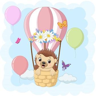 Desenho animado bebê ouriço montando um balão de ar quente