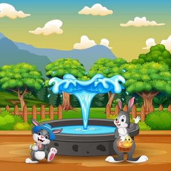 Desenho animado de coelhos felizes perto da fonte