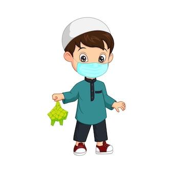 Desenho animado de menino muçulmano feliz com máscara e segurando um ketupat