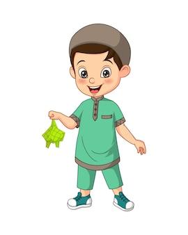 Desenho animado de menino muçulmano feliz segurando um ketupat