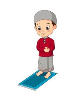 Desenho animado de menino muçulmano rezando no tapete