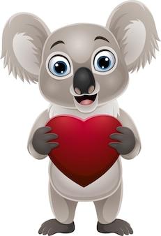 Desenho animado pequeno coala segurando um coração vermelho