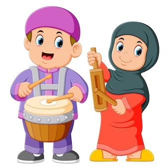 Desenho de criança muçulmana feliz tocando instrumentos musicais tradicionais