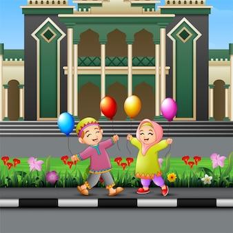 Desenho de crianças muçulmanas feliz jogando na frente de uma mesquita