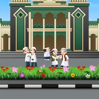 Desenho de crianças muçulmanas feliz na frente de uma mesquita