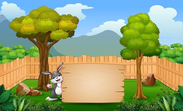 Desenho de um coelho segurando uma placa em branco no parque