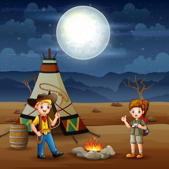 Desenho do menino e da menina explorador acampando no deserto