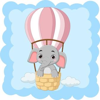 Desenho elefante bebê montando um balão de ar quente