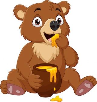 Desenhos animados bebê urso sentado e comendo mel da panela