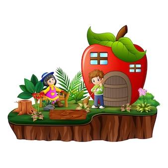 Desenhos animados de crianças felizes com uma casa de maçã na ilha