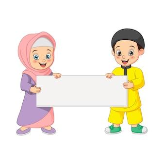 Desenhos animados felizes de crianças muçulmanas segurando um cartaz em branco