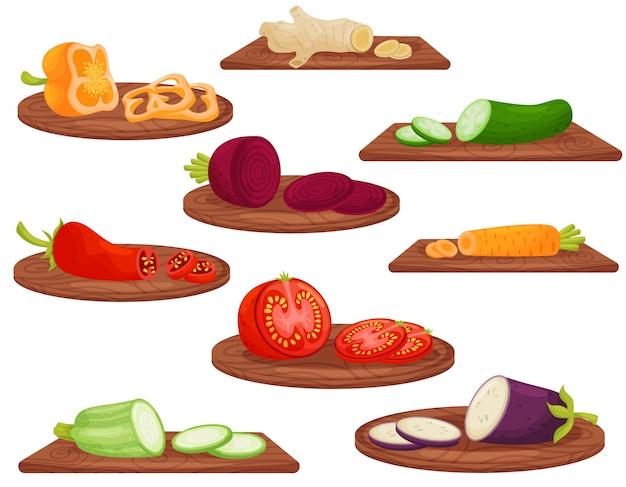 Desenhos animados legumes na tábua de madeira, sobre fundo branco.