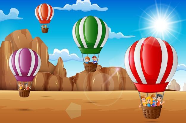 Desenhos animados meninos felizes andando de balão de ar quente no deserto