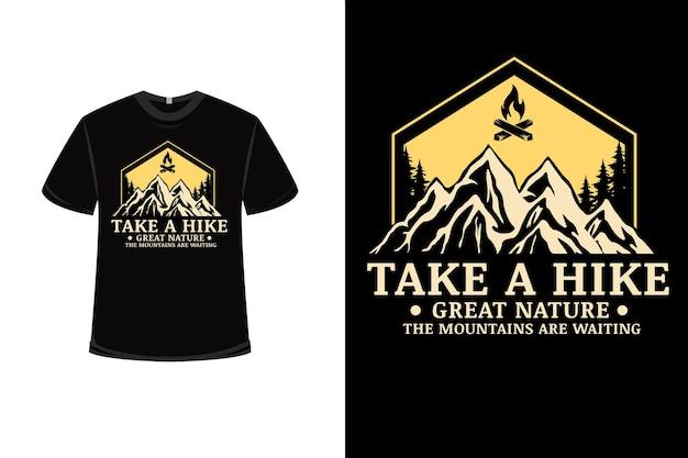 Design de t-shirt com caminhada grande natureza te as montanhas estão esperando em amarelo e creme