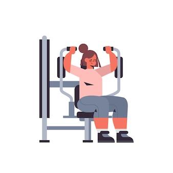 Desportista exercitando-se na menina do aparelho de treinamento fazendo exercícios físicos no conceito de estilo de vida saudável do ginásio
