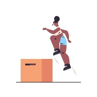 Desportista fazendo agachamento de salto na caixa de agachamento, malhando no conceito de estilo de vida saudável de treinamento de fitness de ginásio