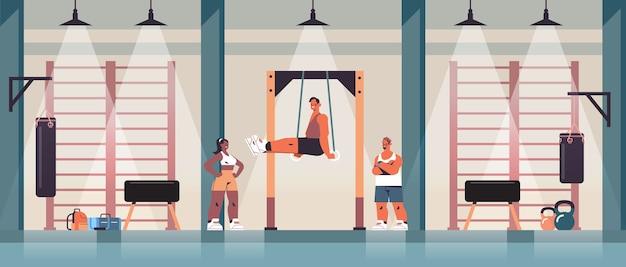 Desportista ginasta fazendo exercícios abdominais homem exercitando-se na barra, exercitando-se, fitness, treinamento, estilo de vida saudável, ginásio, estúdio, interior