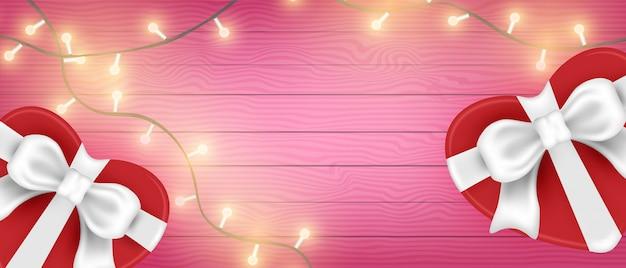 Dia dos namorados banner fundo vista superior. caixa de forma de coração e luz brilhante na mesa de madeira.
