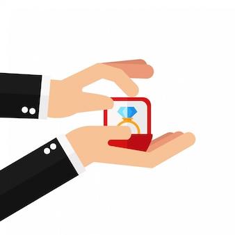 Dia dos namorados. homem está segurando na mão uma caixa aberta com um anel de casamento e diamante