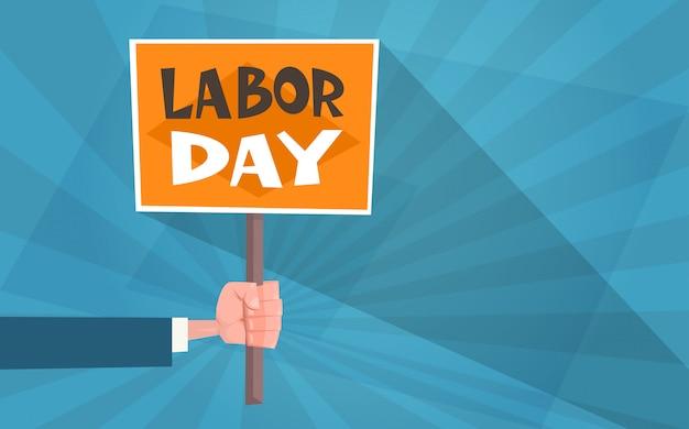Dia internacional do trabalho em cartão de estilo vintage com a mão segurando o cartaz
