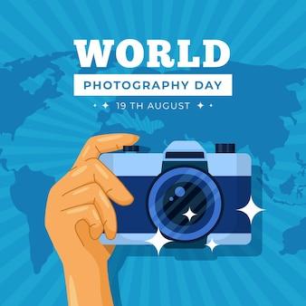 Dia mundial da fotografia com a mão segurando a câmera