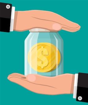 Dinheiro de vidro com moedas de ouro e mãos. salvando moedas de um dólar no mealheiro. crescimento, renda, poupança, investimento. seguro bancário, proteção. símbolo de riqueza. sucesso nos negócios.